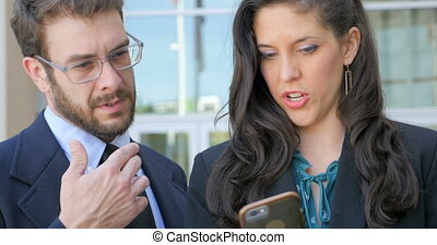 A woman shows a man her smart phone social media social networking or video app