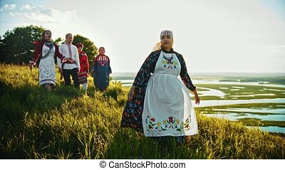 A woman singing a song in russian traditional clothes standing on the field - other people come closer to her