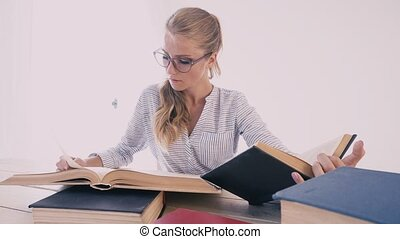 a woman sits at a desk in the Office studying the books is preparing for the exam
