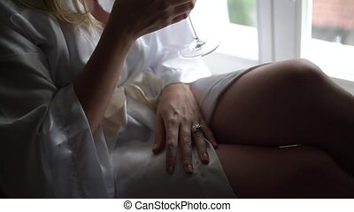 A woman sits at the window in a robe with a glass of champagne
