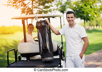 A woman sits behind the wheel of a golf cart, a man stands in the foreground and holds a bag with golf clubs