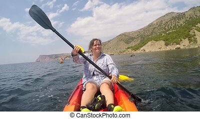 A woman sits in a kayak and paddles with an oar - A woman...