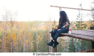 A woman sits on a altitude platform and eats banana and...