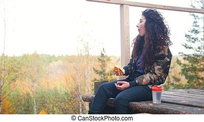 A woman sits on a altitude platform and eats banana. Close...