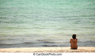 a woman sits on the beach naked looking out to sea