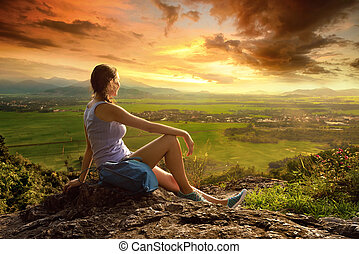 A woman sits on the edge of the cliff and looking at the sun valley and mountains