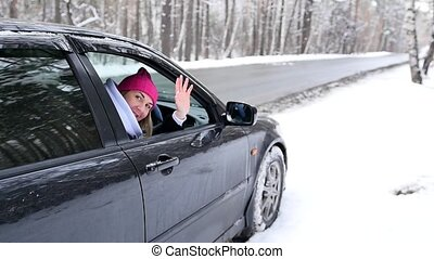 A woman sits with her car and waves her hand, welcoming, against the background of a snowy forest