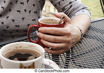 A woman sitting at a garden table with a red cup of coffee