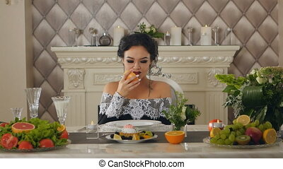 a woman sitting at a table posing with a grapefruit in the hands of