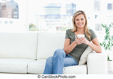 A woman sitting at the side of the couch, with a cup in her hands, a smile and looking forward.