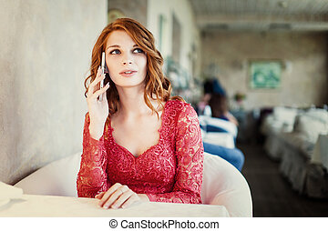 A woman sitting in a cafe with cell phone