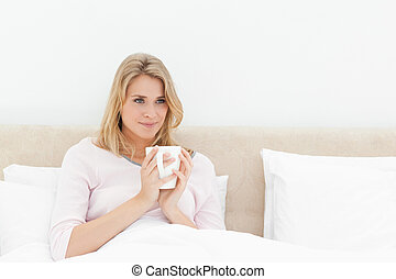 A woman sitting in bed, looking to the side a little, while holding a cup in her hands.