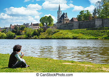 woman sitting in the grass near a river