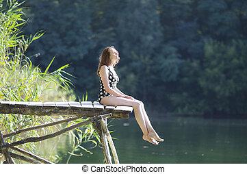A woman sitting on a bridge