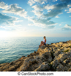 A woman sitting on a cliff by the sea.