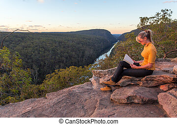 A woman sitting on a rock reading in nature