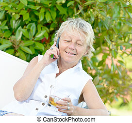 a woman sitting on phone with a drink