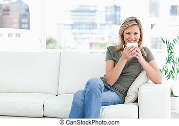 A woman sitting on the couch smiling and looking forward as she holds a mug up to her lips.