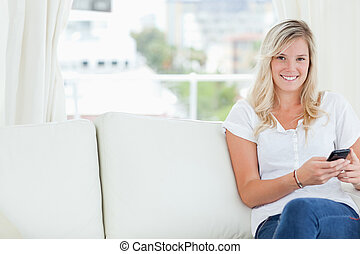 A woman sitting on the couch smiling as she uses her mobile phone while looking at the camera