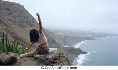 A woman sitting on the edge of a cliff in a pose war...