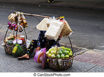 A woman sitting on the road in Vietnam with her portable shop, two baskets, street vendor selling fruits and other products