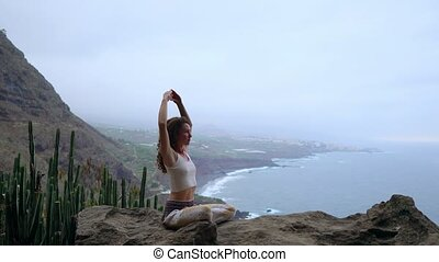 A woman sitting on top of a mountain meditates and makes a...