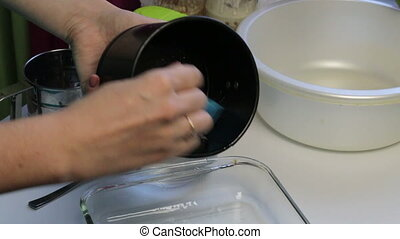 A woman smears a bread baking dish with sunflower oil. Uses a culinary brush. Cooking bread at home.