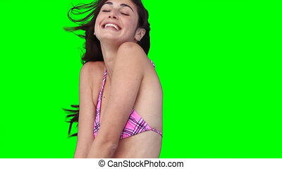 A woman smiles while hopping up and down against a green background
