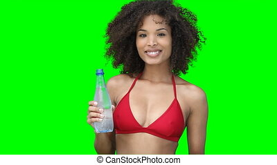 A woman smiling as she drinks water from a bottle