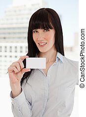 A woman smiling as she holds a business card in front of her