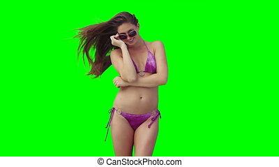 A woman smiling as she wears sunglasses and a bikini