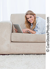 A woman smiling at the camera is holding a tablet