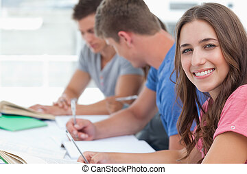 A woman smiling at the camera while her friends sit beside her looking at the homework they have