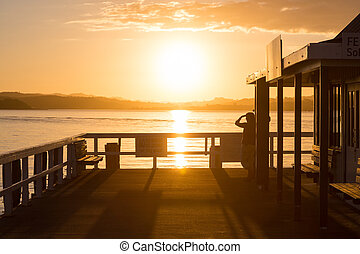A woman standing at a pier and looking into the distance at sunset