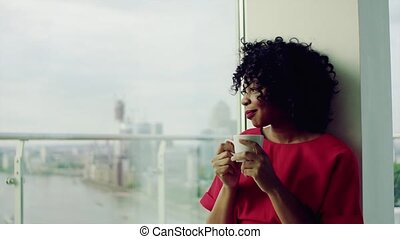 A woman standing by the window against London panorama,...
