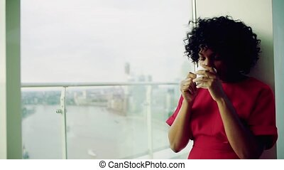 A woman standing by the window against London panorama, holding a cup of coffee.