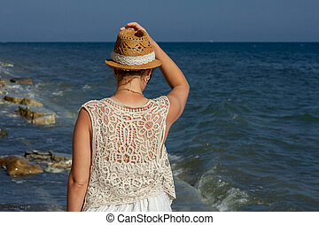 A woman standing in front of water