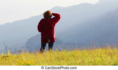 A woman stands on a hillside in autumn day - Woman in red...
