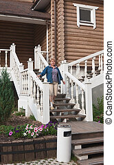 A woman stands on the steps of log cabin
