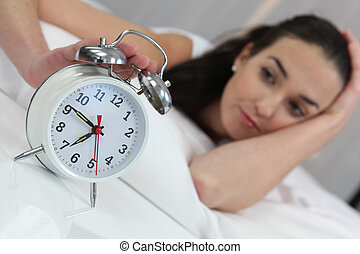 a woman stopping an alarm clock