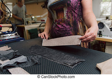 A woman strokes the fabric for further sewing. Tailor ironing clothes