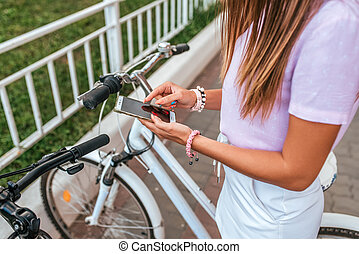 A woman summer stands bicycle, activates application buying rental bicycle in parking lot, in hands of phone. Online selection of route on map in the city. Cycling on weekend. Route map on phone.