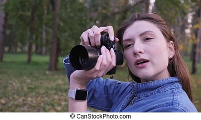 A woman takes pictures on a black compact camera against the background of a beautiful autumn park. Static wide shot