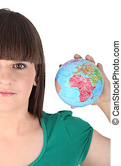 a woman taking a little globe in her hand