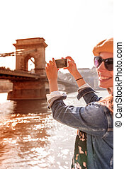A beautiful woman taking pictures of the Szechenyi Bridge in Budapest during sunset.