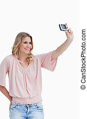 A woman talking a photo of herself with her camera