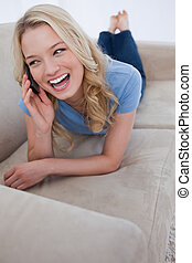 A woman talking on her mobile phone is laughing