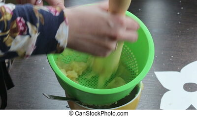 A woman taps boiled apples into applesauce. Uses colander...