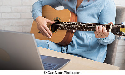 A woman teaches to play the guitar online. Remote music lessons on a laptop