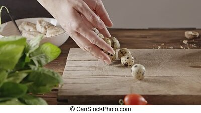 A woman throwing her hands of quail eggs on cutting wooden...